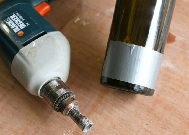 Apply a 2-inch piece of duct or painter's tape on the back of the bottle just above the base